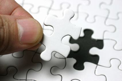 person placing jigsaw puzzle piece